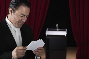 Hispanic man in tuxedo reviewing notecards backstage