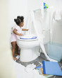 African American girl spreading toilet paper around bathroom