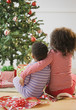 African American brother and sister hugging by Christmas tree