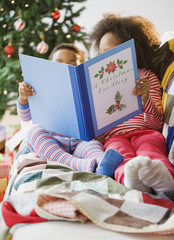 African American brother and sister reading Christmas book