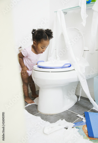 African American girl looking into toilet