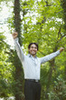 Hispanic businessman in woods with arms outstretched