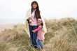 Mother And Daughter Wrapped In Blanket Amongst Dunes On Winter B