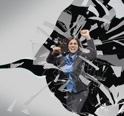 Hispanic businesswoman breaking through glass barrier