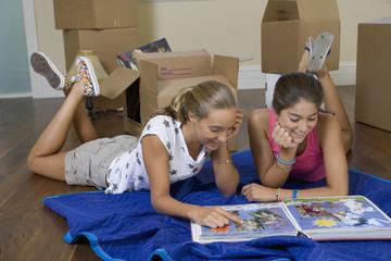 Hispanic teenage girls looking at photograph album