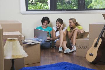 Hispanic teenage girls and woman using laptop