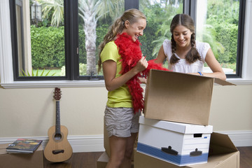 Hispanic teenage girls unpacking cardboard boxes