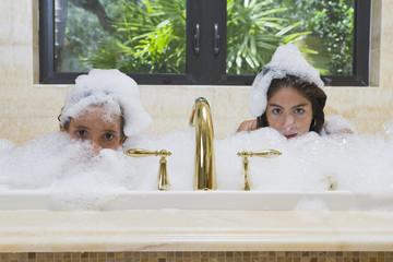 Hispanic teenage girls in bubble bath