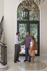Hispanic couple meeting with realtor in foyer