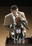 African American man sweating at press conference podium