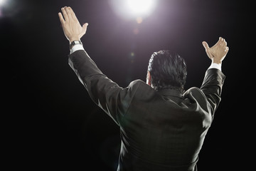 Hispanic man standing with arms raised under spotlight
