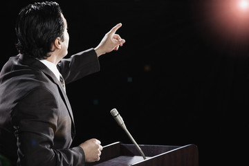 Hispanic man at podium with arm raised