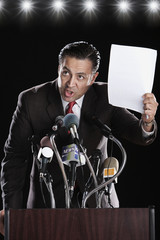 Hispanic man holding paper at press conference podium