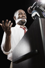 African American man at podium with gag in mouth