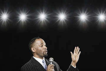African American man holding microphone and gesturing