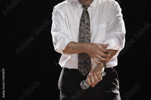 Hispanic man holding microphone and rolling up shirtsleeve