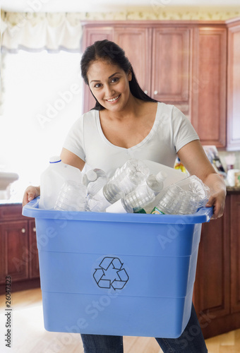 Hispanic woman carrying bin of recyclable bottles
