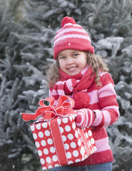 Mixed race girl holding Christmas gift in falling snow