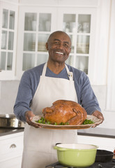 African man holding Thanksgiving turkey