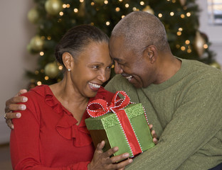 African couple exchanging Christmas gifts