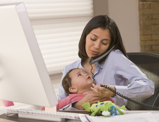 Hispanic mother holding daughter and working