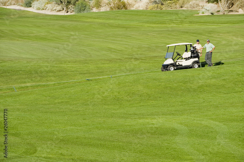 Hispanic men near golf cart on golf course