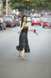Barefoot Asian woman in evening gown running in street