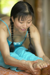 Asian woman on exercise mat doing  yoga