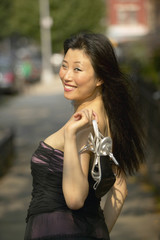 Asian woman in evening gown holding shoes