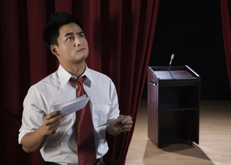 Asian man reviewing notecards backstage and looking nervous
