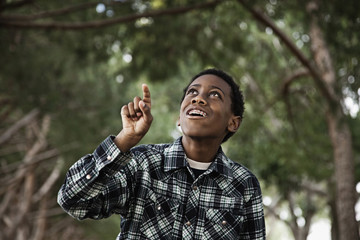 African boy standing in park pointing upwards