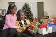 African girl giving grandmother Christmas gift