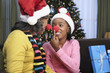 African woman and granddaughter in santa hats and red noses