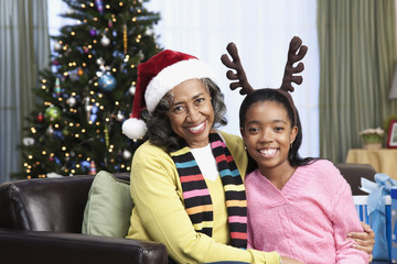 African woman and granddaughter in santa hat and antler headband
