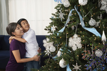 Asian mother hugging son next to Christmas tree
