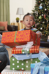 Asian boy opening Christmas gifts