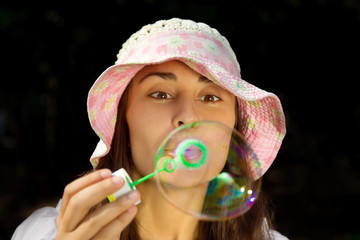 Portrait of a funny young girl blowing bubbles