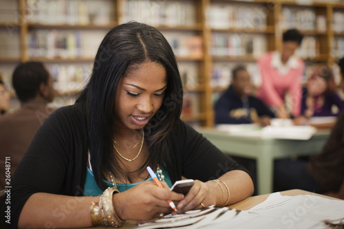 Teenage girl using cell phone in school library