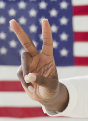 African woman making peace symbol near American flag