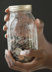African woman holding jar of coins