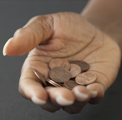 African woman holding handful of pennies