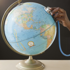 African woman using stethoscope on globe