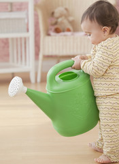 Mixed race baby girl holding watering can