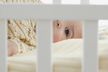 Mixed race baby girl laying in crib