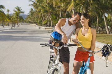 Hispanic couple on bicycles taking rest break