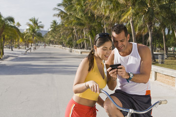 Hispanic couple on bicycles looking at cell phone