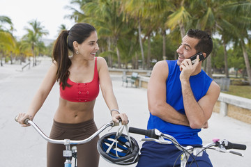 Hispanic man on bicycle talking on cell phone while girlfriend waits