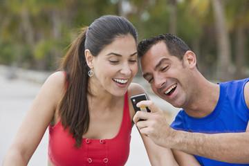 Hispanic man showing girlfriend cell phone