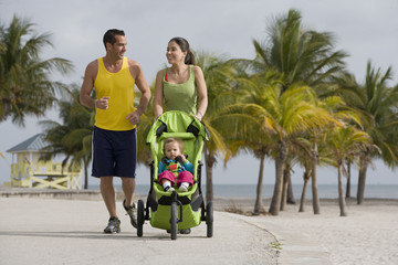 Hispanic couple pushing baby in jogging stroller