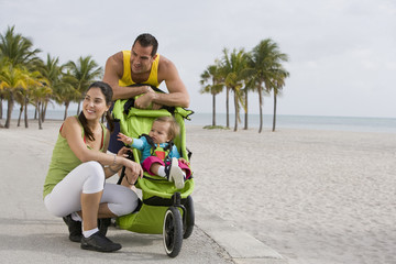 Hispanic couple stopping with baby in jogging stroller